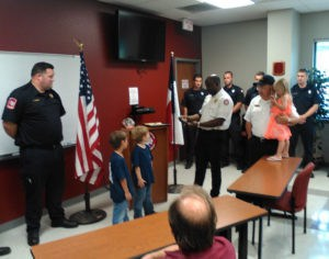 Fire Chief Reggie Cooper honors six year olds Tristan Heath and Warren Jeans for their actions in alerting adults about Hayden Heath, age 3,being in the bottom of the pool.